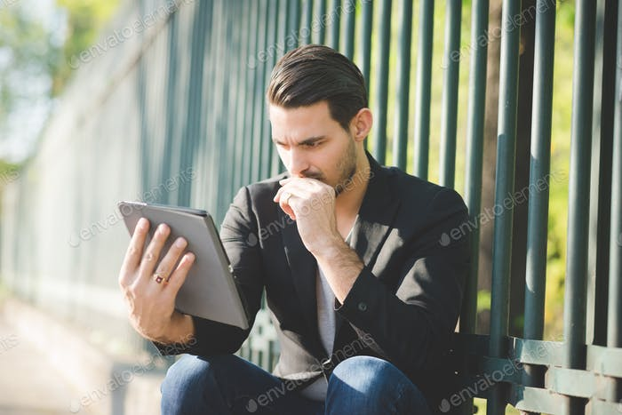 Portrait of a young handsome caucasian man using a tablet