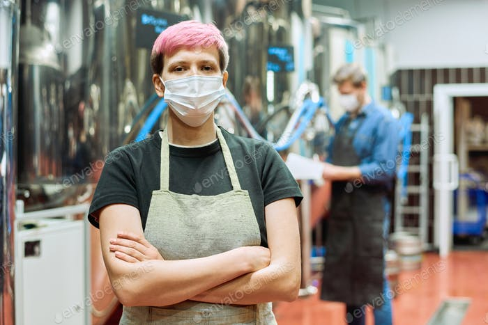 Young female brewer in apron and protective mask crossing arms by chest