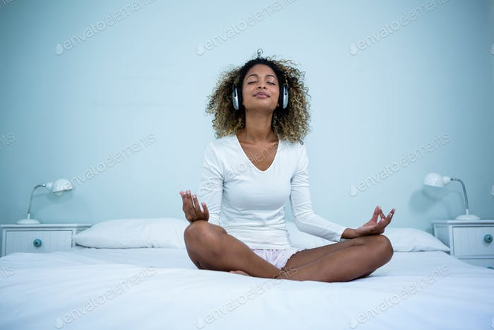 Woman listening to music on head phones while meditating on bed
