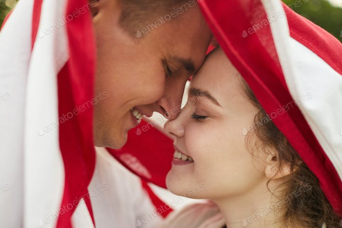 Loving Young Couple Under American Flag