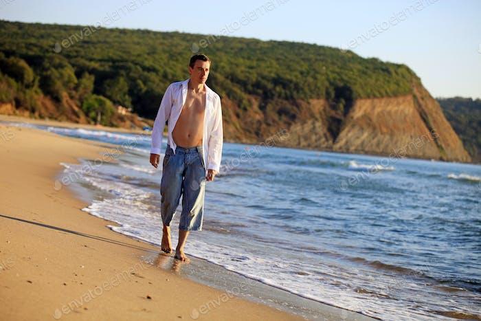 Young man walking along the beach
