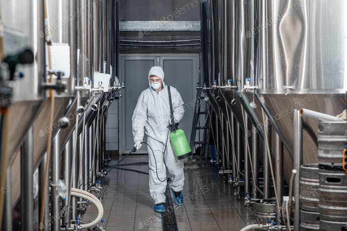 Brewer working with industrial equipment at brewery in protective suit and cleans up