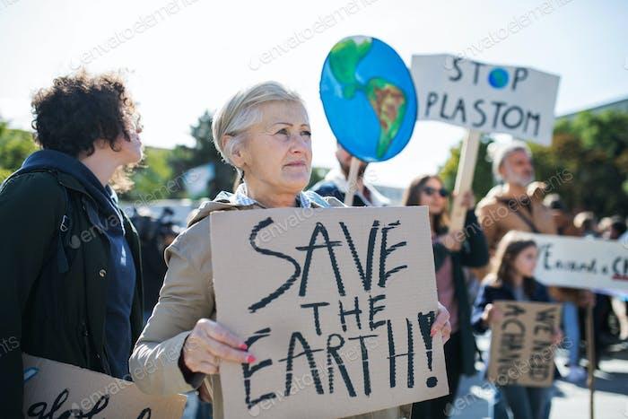 Senior mit Plakat und Plakat zum globalen Streik für den Klimawandel