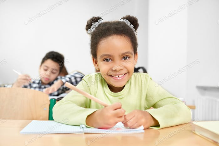Schoolgirl smiling, posing in classroom at primary school
