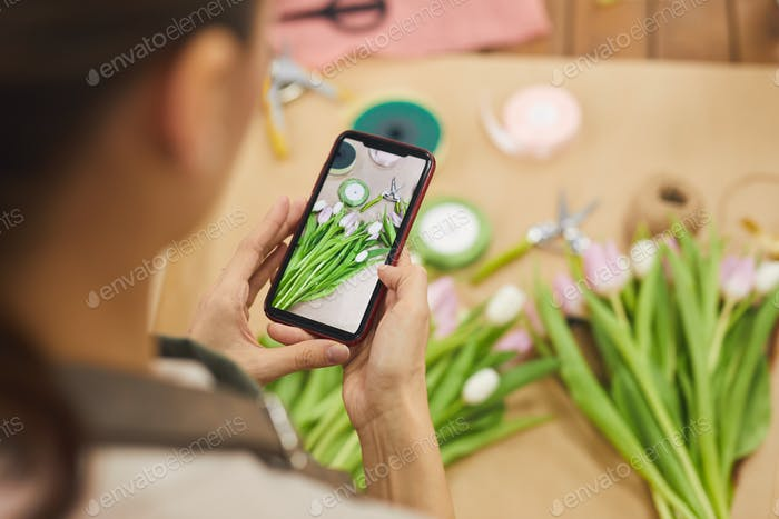 Woman Taking Photo of Flowers