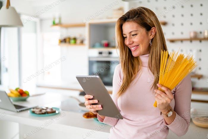 Smiling beautiful woman looking at recipe on digital tablet