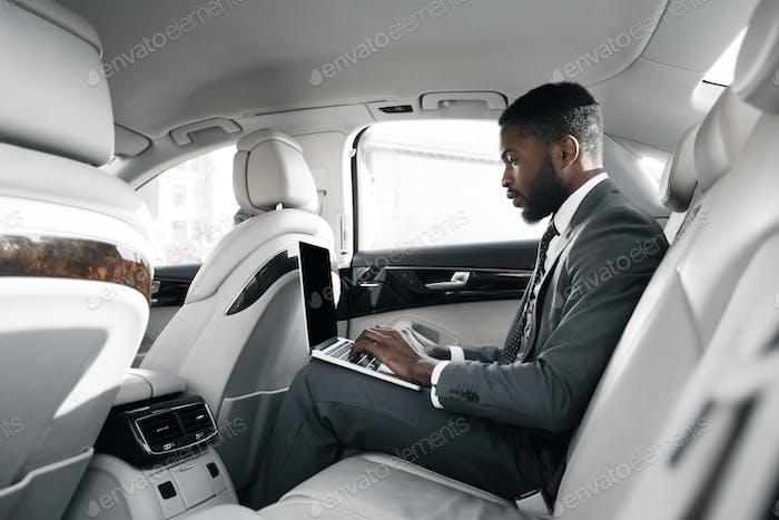 African-american businessman working on laptop in car