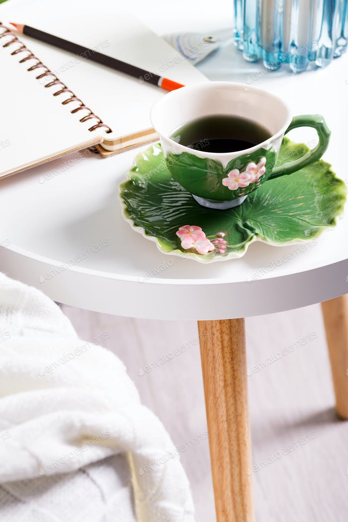 a cup of herbal tea on a table with notepad and candle . Bedroom interior