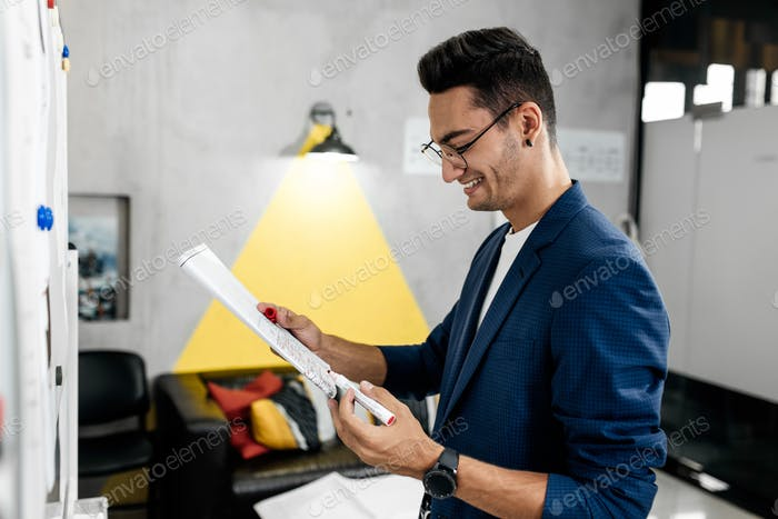 Stylish architect dressed in blue checkered jacket and jeans works with blueprints in the modern