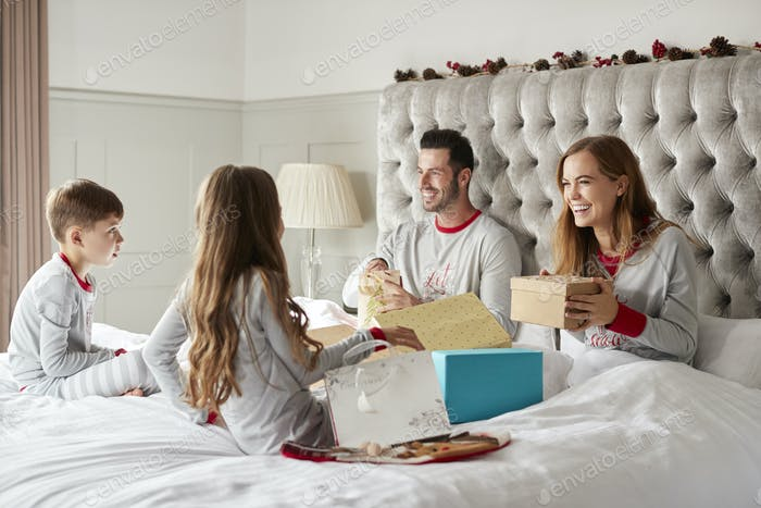 Excited Children Sitting On Parents Bed At Home As Family Open Gifts On Christmas Day