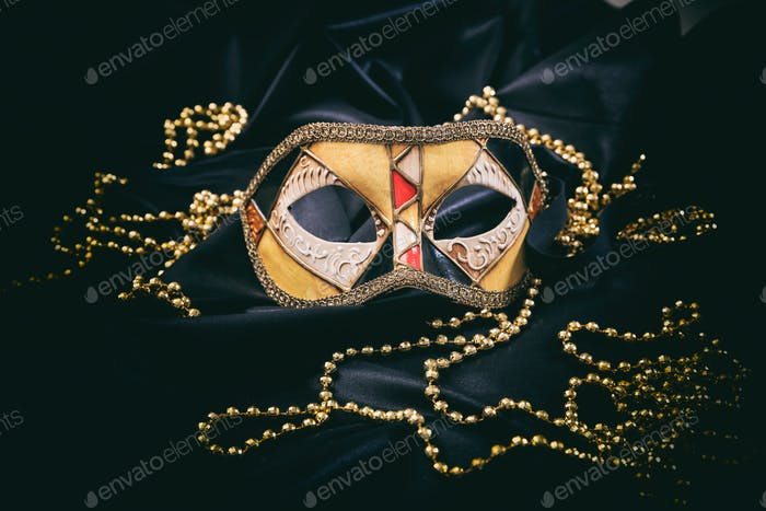 Carnival mask on black satin background