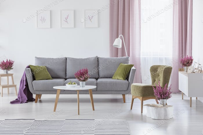 Grey settee with green cushions and purple blanket in real photo