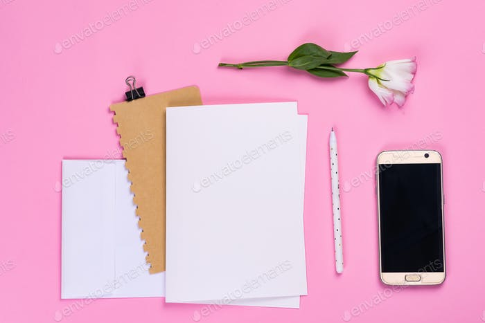 Flowers composition. Paper blank, phone and notebook with eustoma pink flowers on pink background