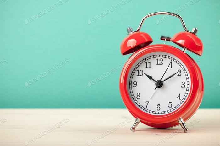 Red alarm clock on wooden table
