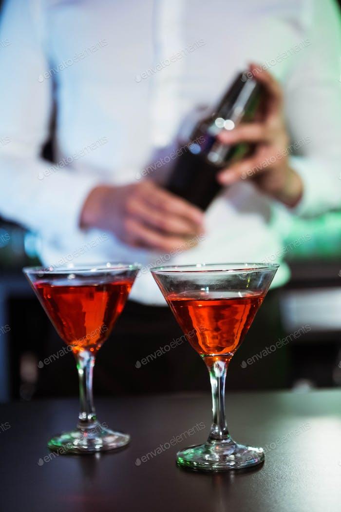 Zwei Gläser Cocktail auf Bartheke und Barkeeper Shaker im Hintergrund