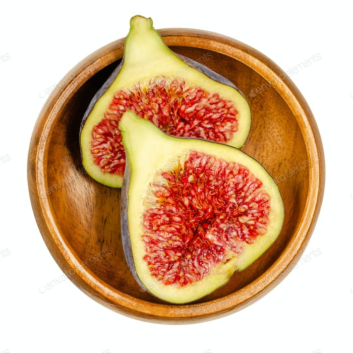 Fresh fig cut in two halves, in a wooden bowl
