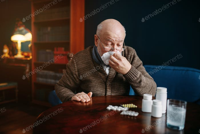 Sick elderly man blows his nose in home office