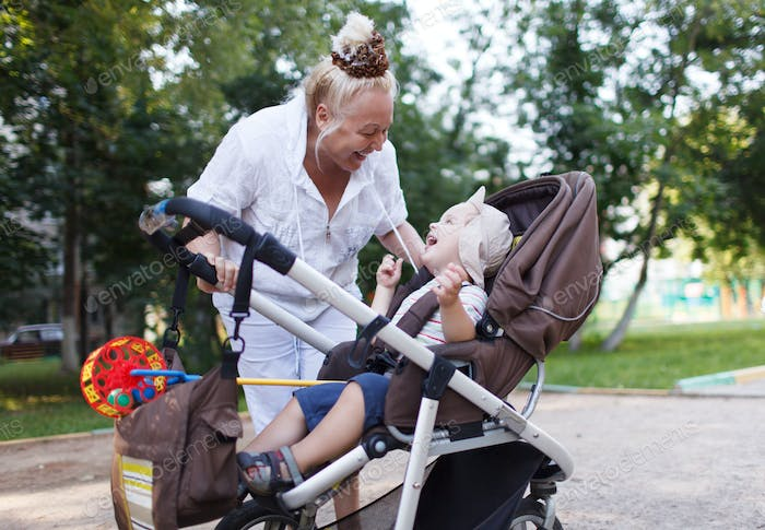 Granny playing with her grandson in pram