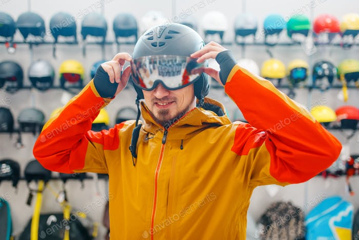 Man trying on helmet for ski or snowboarding