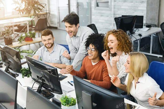Cheerful emotional team reading winning results on monitor