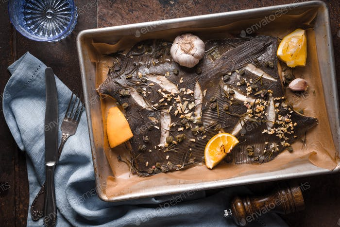 Baking tray with flounder and seasoning on the old background top view