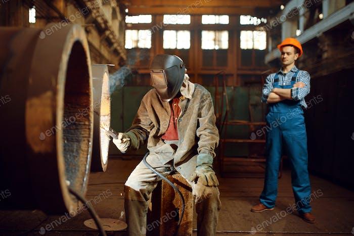 Welder works on factory, worker on background