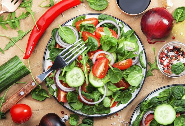 Veganer Frühlingssalat mit Spinat, Kirschtomaten, Maissalat und roten Zwiebeln