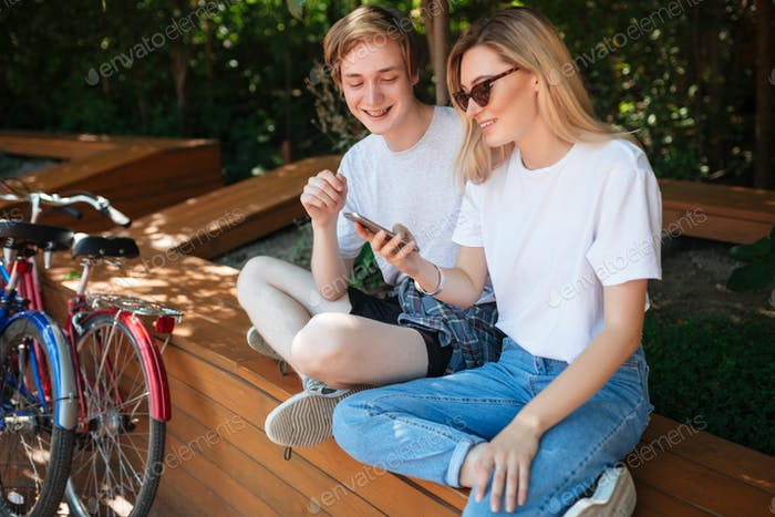 Cheerful couple sitting on bench in park and happily looking in cellphone with two bicycles nearby