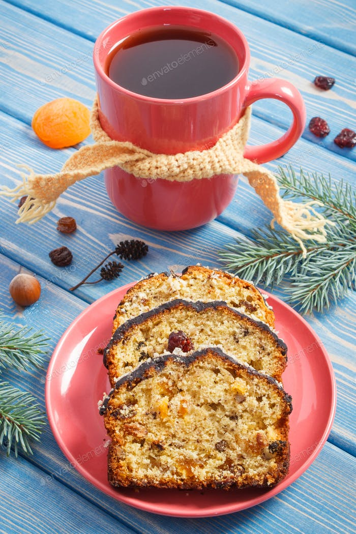 Cup of hot tea, fresh baked fruitcake for Christmas time and spruce branches