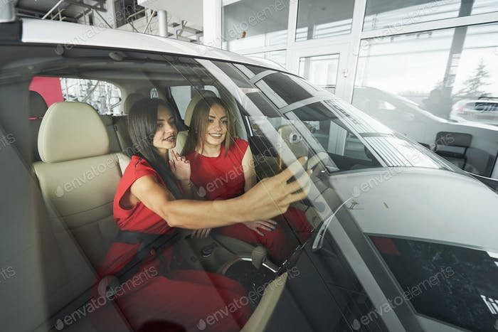 Beautiful young girl twins sitting on the front passenger seats and smiling while posing on camera