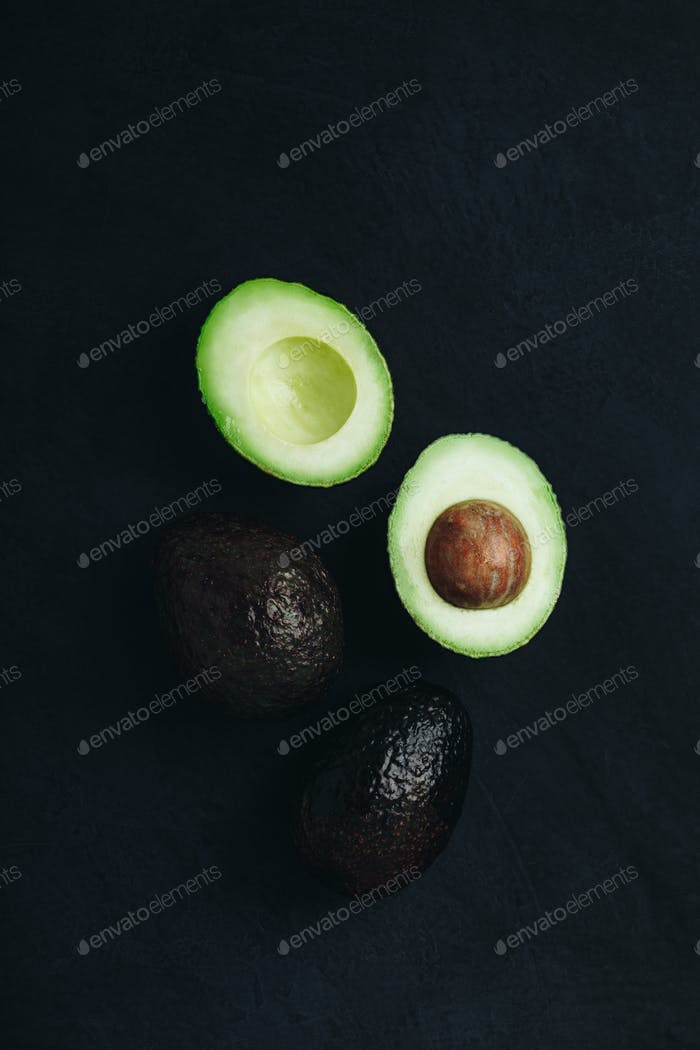 Raw avocado on dark stone background. Fresh green ripe avocado for guacamole.