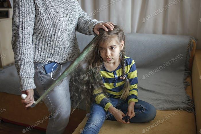 Mutter bereitet Tochter für die Schule vor, kämmt ihre Haare und hört sofort Audio-Chat