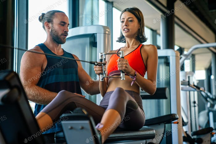 Personal trainer helping woman working out in gym