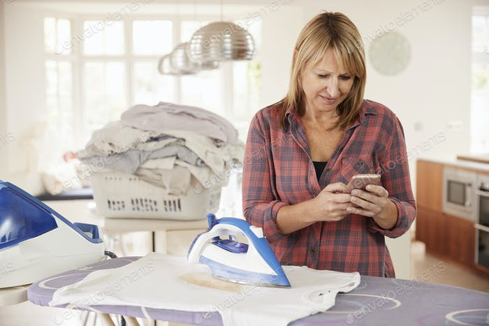 Middle aged woman distracted by phone while ironing t shirt