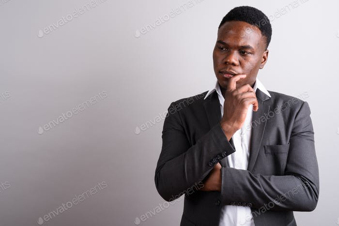 Young African businessman wearing suit against white background