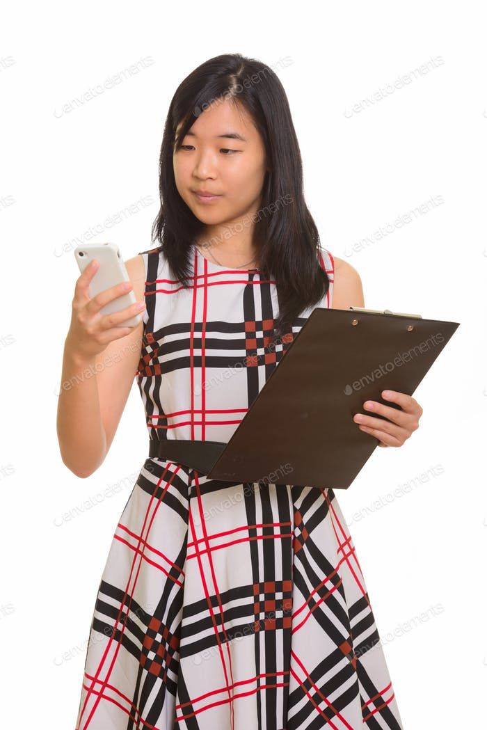 Young beautiful Asian businesswoman holding clipboard while usin