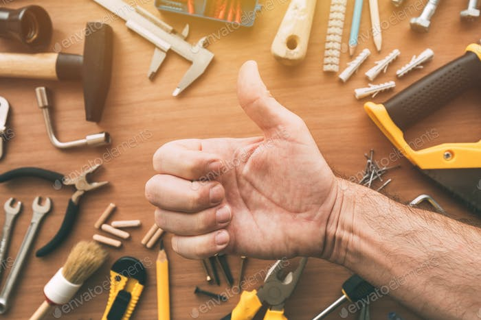 Confident handyman giving thumb up approval hand sign, top view