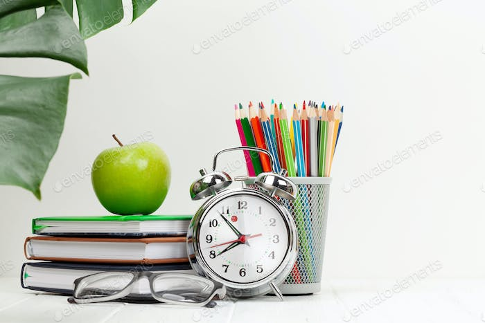 Office workplace with supplies and alarm clock