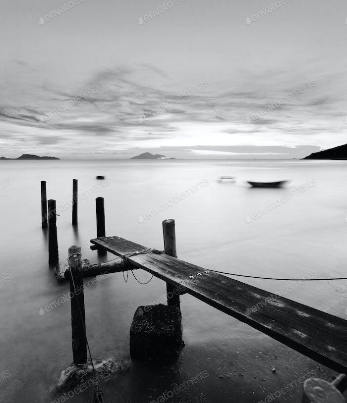 Pier bei Sonnenuntergang in schwarz und weiß