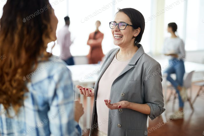 Cheerful Businesswoman Talking to Colleague