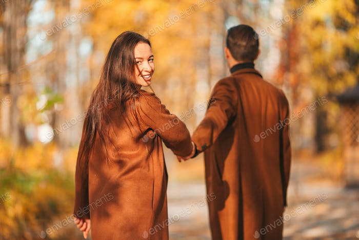 Feliz familia caminando en el parque de otoño en el soleado día de otoño