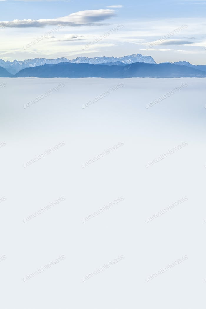 landscape covered in fog with the alps in the background