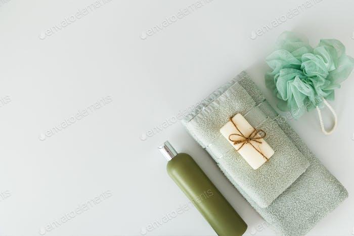 Badetücher mit Pflegeprodukten auf weißem Hintergrund. Flachlage, Draufsicht