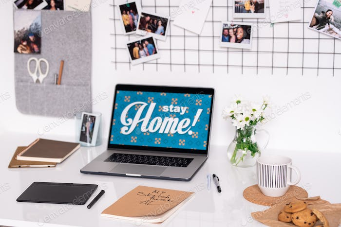 Laptop of designer surrounded by work supplies on desk and photos on wall