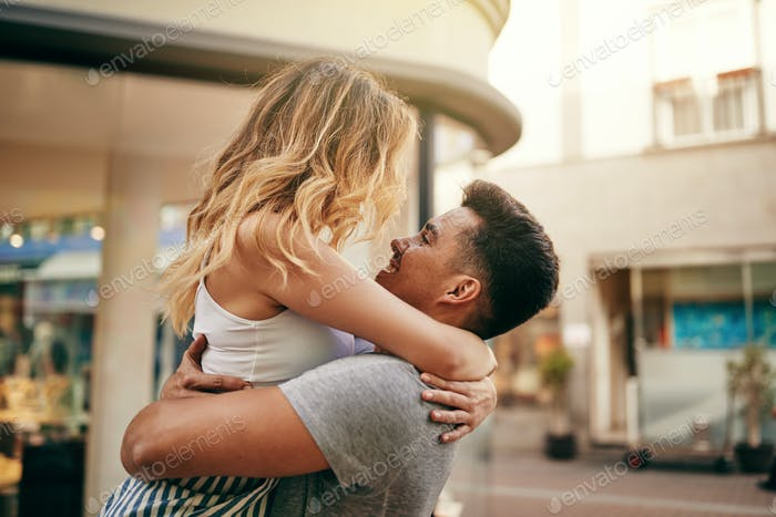 Affectionate young couple hugging on a city street