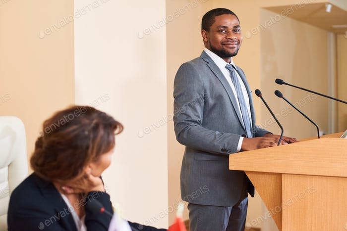 Happy young successful speaker in elegant suit