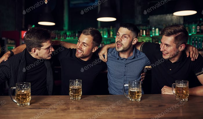 Three friends resting in the pub with beer in hands. Having conversation