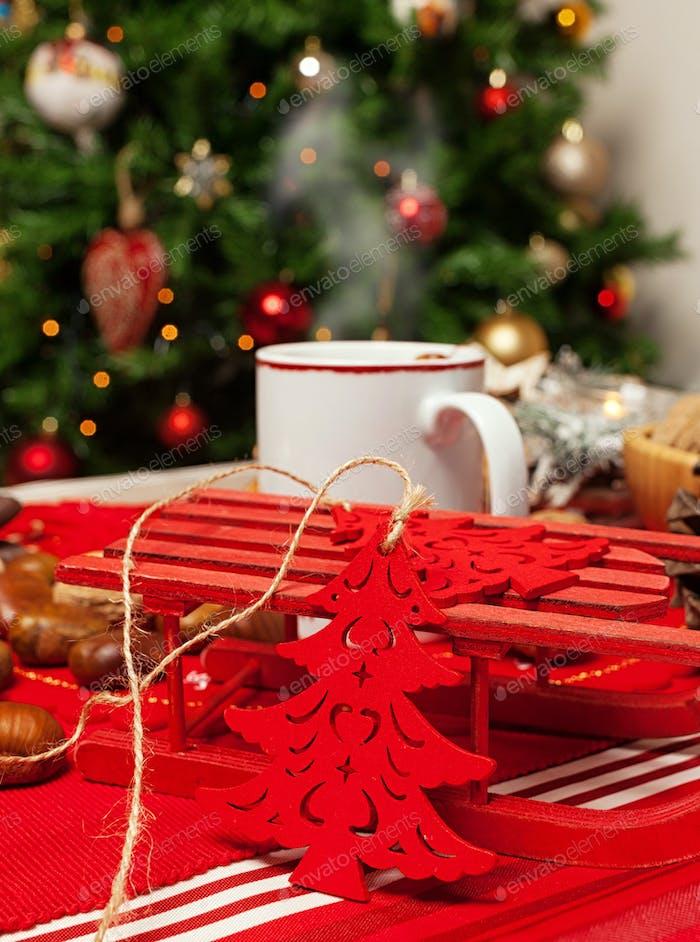 Tasse heißen Tee auf mit hinter Weihnachtsbaum.