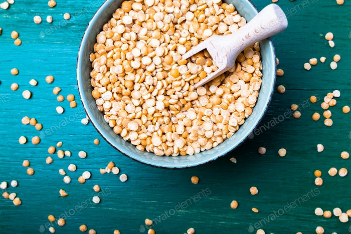 Dry yellow pea in green bowl on green background. Top view.