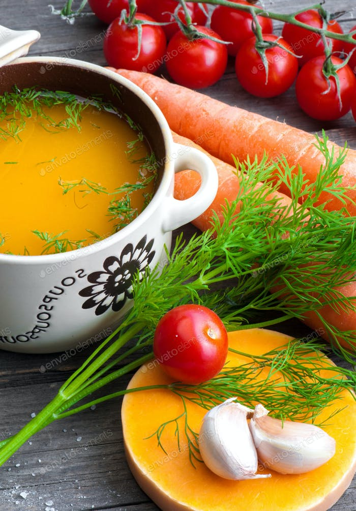 Fresh carrot soup in a jug with raw vegetables.